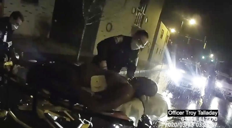 In this image taken from police body camera video provided by Roth and Roth LLP, Rochester police officers prepare to load Daniel Prude into an ambulance on March 23, 2020, in Rochester, N.Y. Prude, a Black man who had run naked through the streets of the western New York city, died of asphyxiation after a group of police officers put a hood over his head, then pressed his face into the pavement for two minutes, according to video and records released Wednesday, Sept. 2, 2020, by the man's family. Prude died March 30 after he was taken off life support, seven days after the encounter with police in Rochester. (Rochester Police via Roth and Roth LLP via AP)
