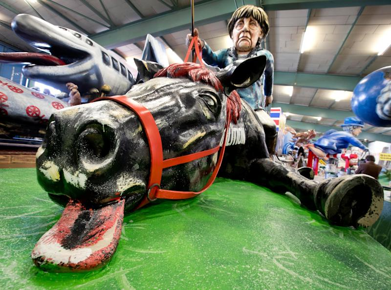 A figure depicting German Chancellor Angela Merkel sitting on a collapsed horse with the inscription 'coalition' is shown during a press preview in a hall of the Mainz carnival club in Mainz, Germany, Feb. 26, 2019. (Photo: Michael Probst/AP)