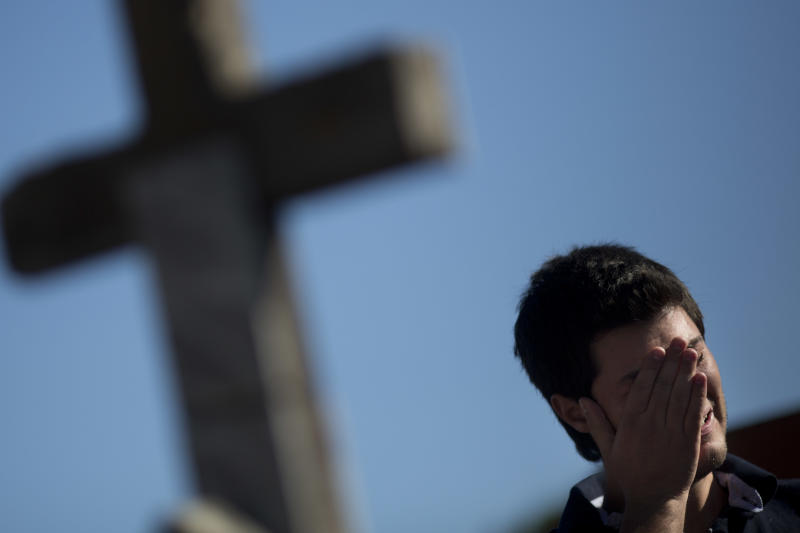 A man cries during the burial of Vinicius Rosado, who died in a nightclub fire, at a cemetery in Santa Maria, Brazil, Monday, Jan. 28, 2013. A fast-moving fire roared through the crowded, windowless Kiss nightclub in this southern Brazilian city early Sunday, killing more than 230 people. Many of the victims were under 20 years old, including some minors. (AP Photo/Felipe Dana)