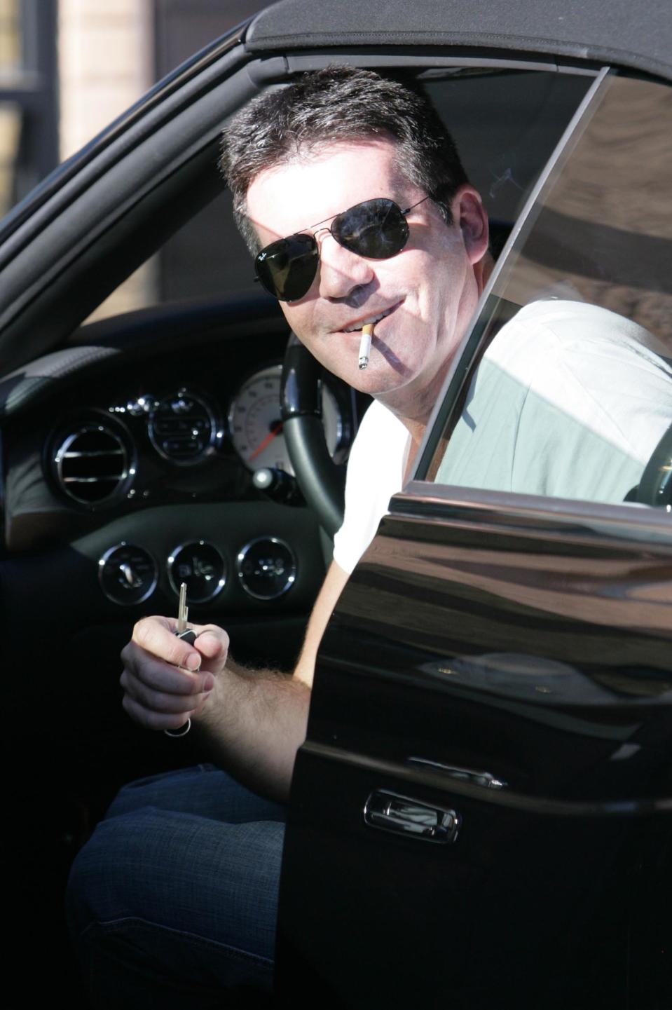 REVOLUTIONPIX/©2010 RAMEY PHOTO Simon Cowell Los Angeles March 14 2010 Simon Cowell and girlfriend Mezhgan Hussainy drive to Malibu Market, in a Black Luxury English Convertible Bentley Azure, priced at over 340 000 usd, to have pictures taken with fans, chat Howie Mandel and go shopping at John Varvatos Revpix (Photo by Philip Ramey/Corbis via Getty Images)