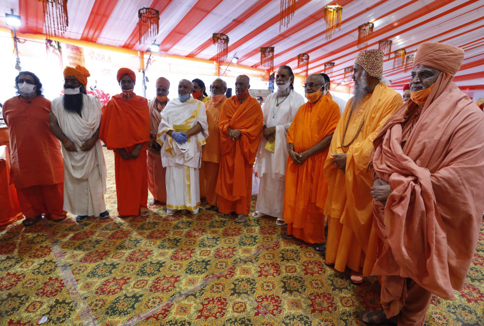 Hindu priests gather for a groundbreaking ceremony of a temple dedicated to the Hindu god Ram in Ayodhya, India, Wednesday, Aug. 5, 2020. The coronavirus is restricting a large crowd, but Hindus were joyful before Prime Minister Narendra Modi breaks ground Wednesday on a long-awaited temple of their most revered god Ram at the site of a demolished 16th century mosque in northern India. (AP Photo/Rajesh Kumar Singh)