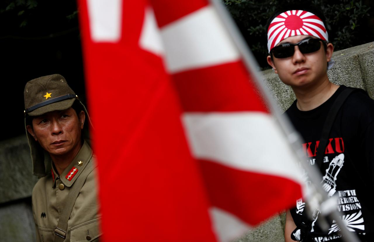 A man dressed as Japanese imperial army soldier and a man wearing a rising sun flag headband stand behind a rising sun flag in front of Yasukuni Shrine on the anniversary of Japan's surrender in World War Two in Tokyo, Japan, August 15, 2016.   REUTERS/Kim Kyung-Hoon TPX IMAGES OF THE DAY