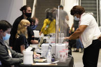 People register before voting early at the State Farm Arena on Monday, Oct. 12, 2020, in Atlanta. (AP Photo/Brynn Anderson)