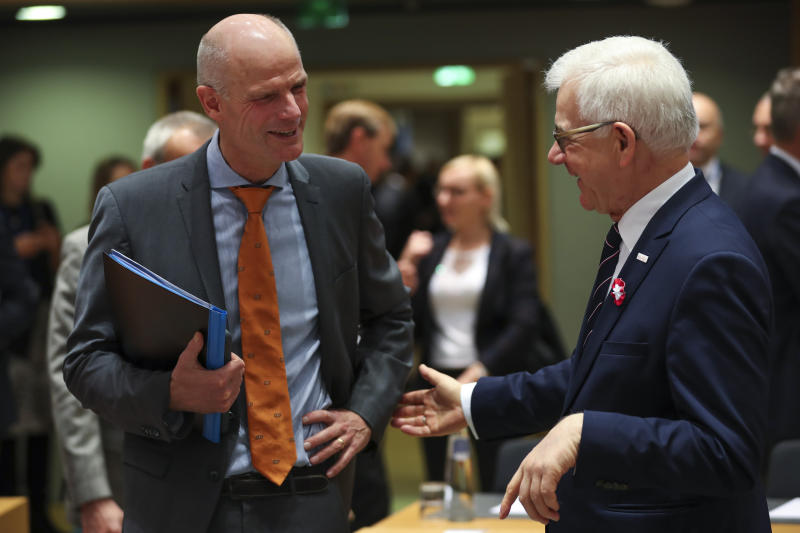 Dutch Foreign Minister Stef Blok, left, talks to Polish Foreign Minister Jacek Czaputowicz during an European Foreign Affairs Ministers meeting at the Europa building in Brussels, Monday, Nov. 11, 2019. European Union foreign ministers are discussing ways to keep the Iran nuclear deal intact after the Islamic Republic began enrichment work at its Fordo power plant. (AP Photo/Francisco Seco)