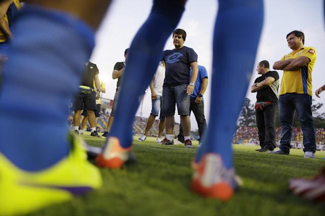 In this Oct. 18, 2014 photo, Hector Marecos, soccer coach for the Deportivo Capiata team, center, gives instructions to his players before a local league match against Cerro Porteno in Capiata, Paraguay. The young soccer club formed six years ago beat Boca 1-0 at its famed La Bombonera stadium in Buenos Aires, and will face them in a second leg match on Thursday, Oct. 23. (AP Photo/Jorge Saenz)