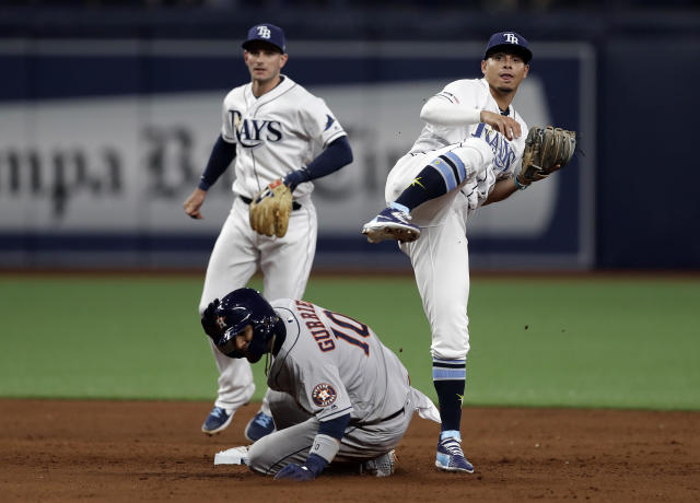 Tampa Bay Rays shortstop Willy Adames, right, and second baseman Daniel Robertson, left, team up to turn a double play on Houston Astros' Yuli Gurriel (10) and Josh Reddick during the sixth inning of a baseball game Friday, March 29, 2019, in St. Petersburg, Fla. (AP Photo/Chris O'Meara)