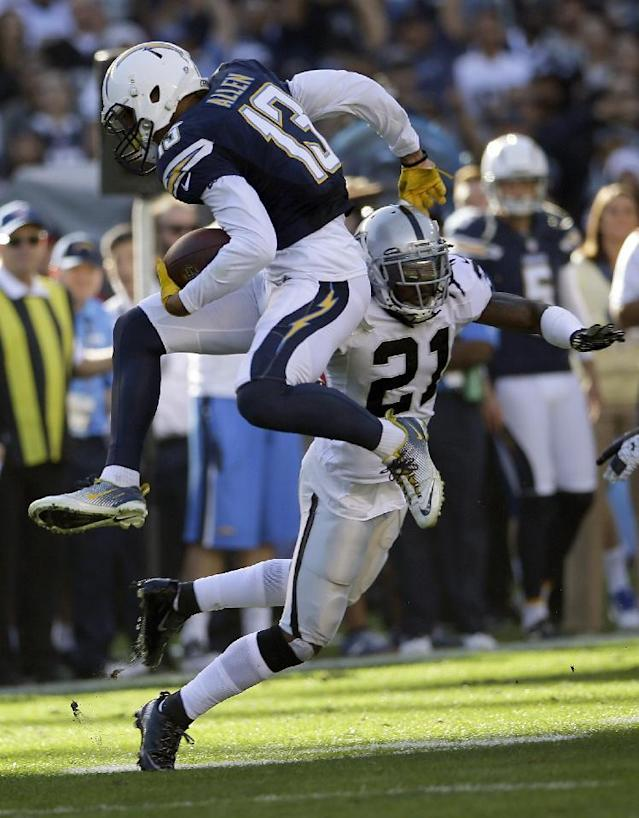 San Diego Chargers wide receiver Keenan Allen, left, runs past Oakland Raiders cornerback Mike Jenkins during the first half of an NFL football game on Sunday, Dec. 22, 2013, in San Diego. (AP Photo/Lenny Ignelzi)