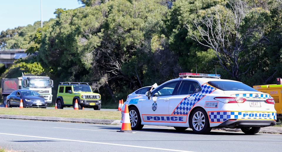 Australian Defence Force (ADF) personnel and Queensland Police process commuters crossing the Queensland-New South Wales state border at Coolangatta, QLD, Wednesday, August 25, 2021. Source: AAP