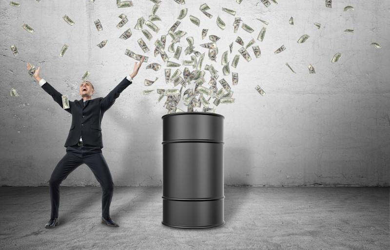 An oil barrel with money spewing out of it with a happy man celebrating next to it.