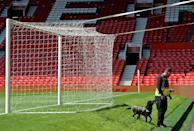 A police sniffer dog searches behind one of the goals at Old Trafford stadium after the Manchester United-Bournemouth match was abandoned (AFP Photo/Oli Scarff)