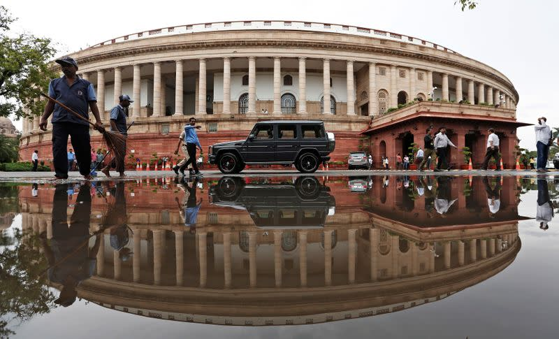 Indian parliament building is reflected in a puddle after the rain in New Delhi
