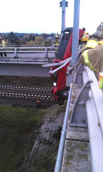 This image provided by the Beaverton Police Department shows a red pickup truck dangling from the Denney Road overpass near highway 217 outside Beaverton, Oregon as emergency workers respond to the scene Saturday afternoon Nov. 24, 2012. The driver has been identified as Matthew Alan Hamilton 38 years old of Beaverton. He was taken to the hospital with unkown injuries after being plucked from the truck by firefighters. Hamilton has been arrested for DUI, driving while suspended for a previous misdemeanor DUI. (AP Photo/Beaverton Police Department)
