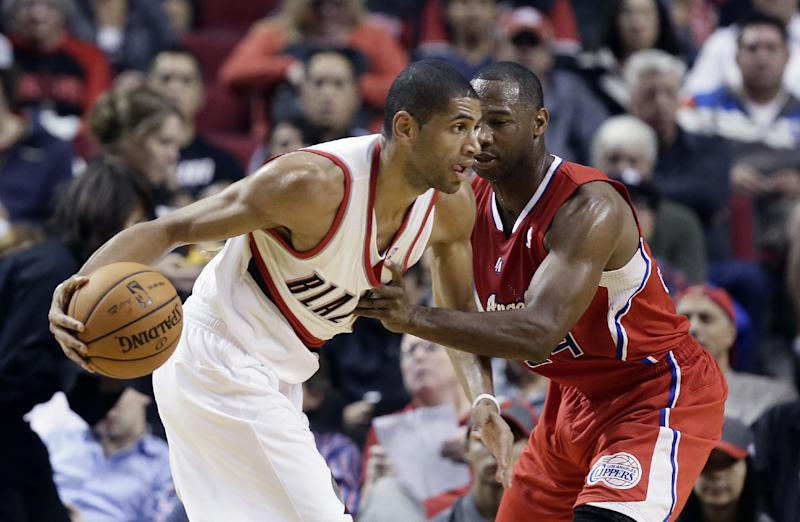 Portland Trail Blazers forward Nicolas Batum, left, from France, drives on Los Angeles Clippers guard Willie Green during the first half of an NBA preseason basketball game in Portland, Ore., Monday, Oct. 7, 2013. (AP Photo/Don Ryan)