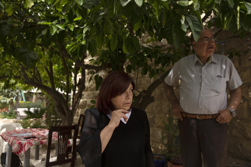 Samira Dajani and her husband, Adel Budeiri, stand in the shade of a tree in the garden of their home, where she has lived since childhood, in the Sheikh Jarrah neighborhood of east Jerusalem, Sunday, May 9, 2021. They are one of dozens of Palestinian families in east Jerusalem at risk of losing their homes to Jewish settler groups following a decades-long legal battle. (AP Photo/Maya Alleruzzo)