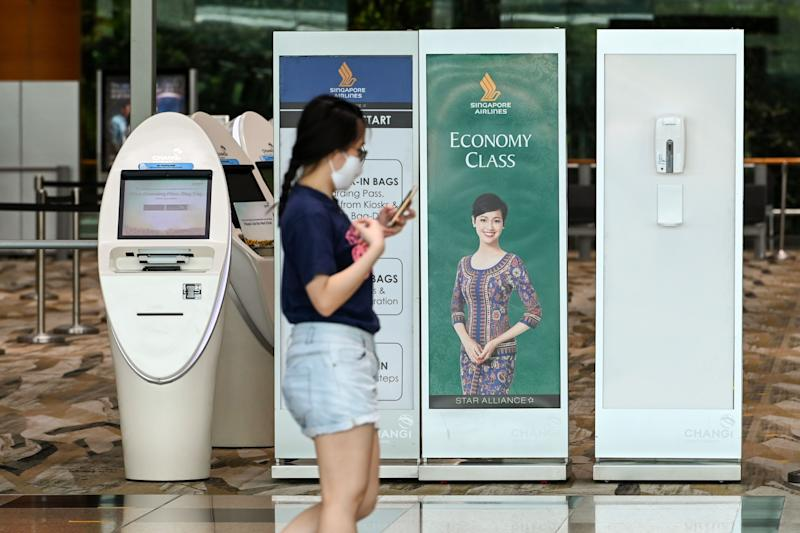 "A woman walks past a Singapore Airlines check-in counter at a Changi International Airport terminal in Singapore on September 11, 2020. - Singapore Airlines said on September 10 it was cutting about 4,300 jobs -- around 20 percent of its workforce -- due to the coronavirus, and warned any recovery would be ""long and fraught with uncertainty"". (Photo by Roslan RAHMAN / AFP) (Photo by ROSLAN RAHMAN/AFP via Getty Images)"