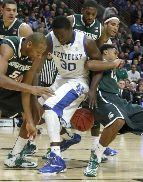 Michigan State center Adreian Payne (5), Kentucky forward Julius Randle (30) and Michigan State guard Gary Harris, right, struggle for a loose ball during the first half of an NCAA college basketball game Tuesday, Nov. 12, 2013, in Chicago. (AP Photo/Charles Rex Arbogast)