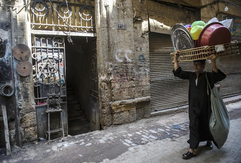A man carries dishes past a Star of David decorating the door of a home in the Jewish quarter of the Egyptian capital, Cairo, on June 25, 2015 (AFP Photo/Khaled Desouki)