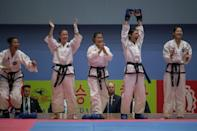 In a photo taken on September 21, 2017 team members from North Korea react following their win against Russia fight during the womens team event of the 20th ITF World Taewondo Championships in Pyongyang