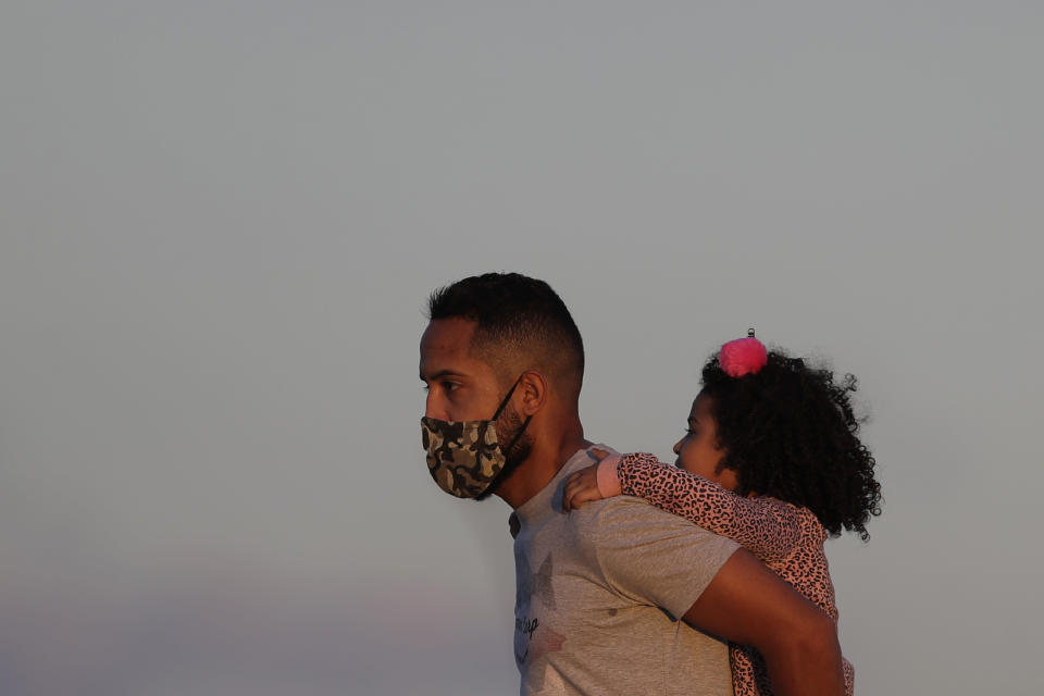 A child gets a piggy back ride from her father as the sun begins to set in Cruzeiro Square in Brasilia, Brazil, Friday, July 31, 2020. People gathered outdoors in the late afternoon as authorities eased the restrictions related to the new coronavirus, despite that Brazil's official COVID-19 death toll is the second highest in the world after the United States. (AP Photo/Eraldo Peres)