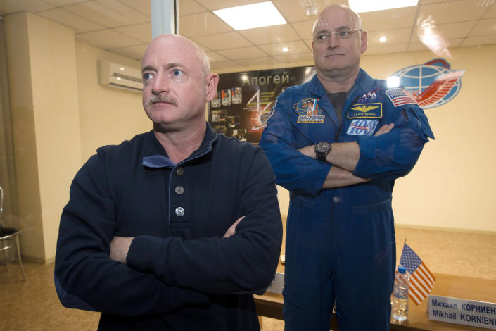 FILE - In this March 26, 2015 file photo, U.S. astronaut Scott Kelly, right, crew member of the mission to the International Space Station, stands behind glass in a quarantine room, behind his brother, Mark Kelly, also an astronaut, after a news conference in the Russian-leased Baikonur, Kazakhstan cosmodrome. Nearly a year in space put Scott Kelly's immune system on high alert and changed the activity of some of his genes compared to his Earth-bound identical twin, according to a report released on Friday, Feb. 15, 2019. (AP Photo/Dmitry Lovetsky)