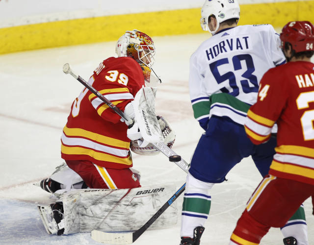 Calgary Flames goalie Cam Talbot makes a save as Vancouver Canucks Bo Horvat looks for the rebound during the second period of an NHL hockey game in Calgary, Alberta, Sunday, Dec. 29, 2019. (Larry MacDougal/The Canadian Press via AP)