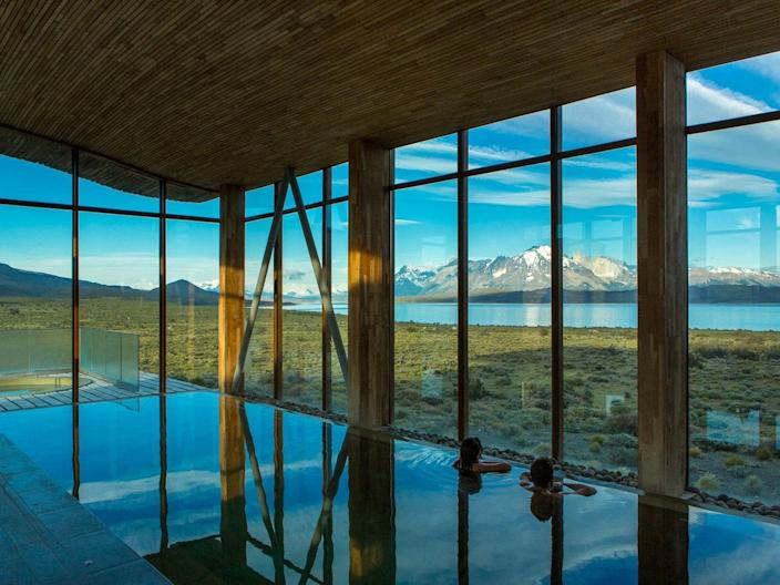 """<p>Set atop a bluff where the South American <em>pampa</em> (fertile plain) meets Lake Sarmiento, the 40-room <a href=""""https://www.cntraveler.com/hotels/chile/torres-del-paine-national-park/tierra-patagonia-hotel---spa?mbid=synd_yahoo_rss"""" rel=""""nofollow noopener"""" target=""""_blank"""" data-ylk=""""slk:Tierra Patagonia"""" class=""""link rapid-noclick-resp"""">Tierra Patagonia</a> is exactly where we'd want to find ourselves between the whipping winds: Clad in lenga beechwood and banked with earth, the walls of this low-slung hotel barely register the gales blowing over from Patagonia's Southern Ice Field. It's not all rough and tumble, though. Interiors at the hotel are spare but cozy, with wide, light wood-framed windows and white finishes throughout, and even a well-stocked library. Depending on your fitness level, set up a half- or full-day excursion to the Paso de Agostini, or the French Valley, to both get off-grid <em>and</em> have a dream setting to return to after long days hiking and biking.</p> <p><strong>Book now</strong>: <a href=""""https://skylark.com/destinations/south-america/chile/patagonia/hotels/tierra-patagonia?utm_medium=partner&utm_source=cnt&utm_content=tierrapatagonia"""" rel=""""nofollow noopener"""" target=""""_blank"""" data-ylk=""""slk:skylark.com"""" class=""""link rapid-noclick-resp"""">skylark.com</a></p>"""
