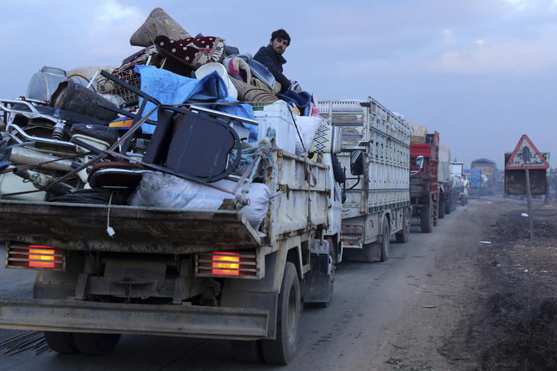 A man rides in a truck as civilians flee a Syrian military offensive in Idlib province on the main road near Hazano, Syria, Tuesday, Dec. 24, 2019. Syrian forces launched a wide ground offensive last week into the northwestern province of Idlib, which is dominated by al-Qaida-linked militants. The United Nations estimates that some 60,000 people have fled from the area, heading south, after the bombings intensified earlier this month. (AP Photo/Ghaith al-Sayed)