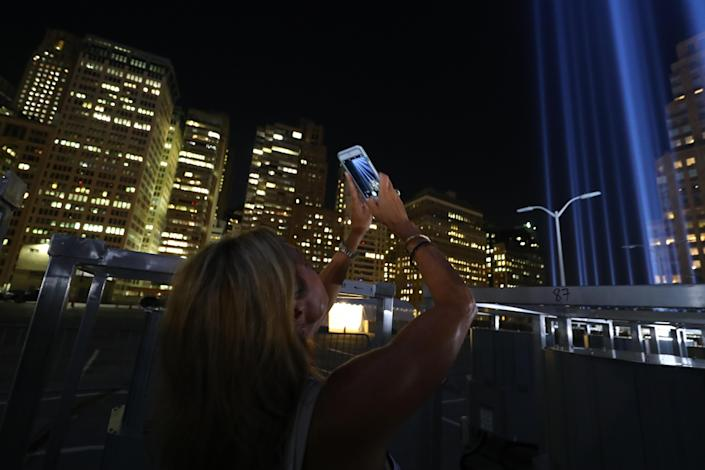 <p>A woman takes a photo of the Tribute in Light with her mobile device from a rooftop on Sept. 5, 2018. (Photo: Gordon Donovan/Yahoo News) </p>