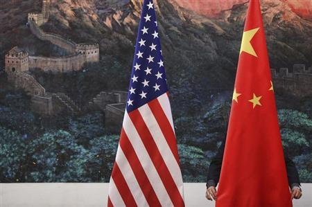 A Chinese man adjusts a China flag before a news conference attended by Chinese Foreign Minister Yang Jiechi and U.S. Secretary of State Hillary Clinton in Beijing