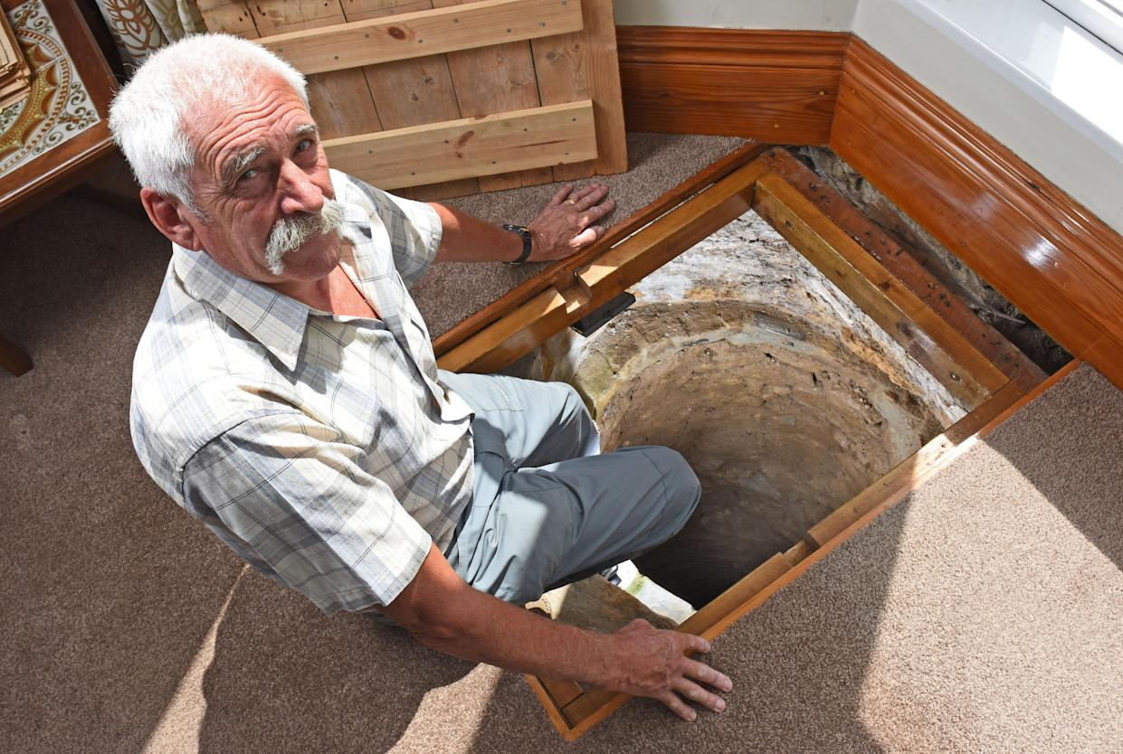 CATERS NEWS (PICTURED - Colin Steer sat on the edge of his well) - A grandad has spent the last decade digging out a 17ft deep medieval well in his living room after noticing a slight dip in the floor when redecorating. Colin Steer, from Plymouth, discovered the well after he noticed a dip in the floor while redecorating his living room ten years ago and has since spent the last decade digging out the 17ft well. The 70-year-old believes that the well could date back to medieval times after discovering an old sword while digging out the well and plans of the site suggests that the well could date back to the 1500s. Colin said: