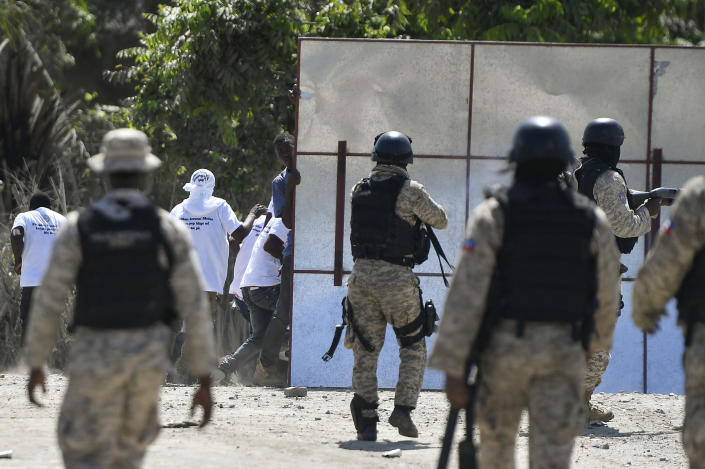 Supporters of slain Haitian President Jovenel Moise are blocked by security forces from attending Moise's funeral outside the former leader's family home in Cap-Haitien, Haiti, Friday, July 23, 2021. Moise was assassinated at his home in Port-au-Prince on July 7. (AP Photo/Matias Delacroix)