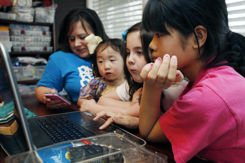 "In this April 4, 2013 photograph, the Smith women, from left, mother Niki Smith, GiGi, 3, Macy Jade, 7 and Guan Ya, 14, use Google Translate on the family laptop to ""speak"" with their new daughter, Guan Ya, in their Rienzi, Miss., home. The Smiths and their children are using the Google Translate program to communicate almost exclusively with Guan Ya, who is deaf. The family uses iPhones, iPods and a laptop, all loaded with the program to write in either English that translates to Chinese or vice-a-versa. (AP Photo/Rogelio V. Solis)"