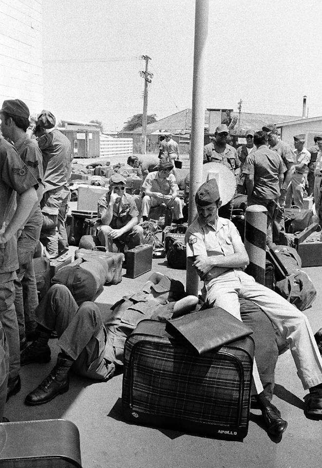 In this March 27, 1973 photo, an American GI takes a nap atop his luggage as he and other troops wait to begin out processing at Camp Alpha in Saigon, as withdrawal of U.S. troops resume after a 10-day dispute over POWs. All U.S. troops are due out Thursday. As the last U.S. combat troops left Vietnam 40 years ago, angry protesters still awaited them at home. North Vietnamese soldiers took heart from their foes' departure, and South Vietnamese who had helped the Americans feared for the future. While the fall of Saigon two years later — with its indelible images of frantic helicopter evacuations — is remembered as the final day of the Vietnam War, Friday marks an anniversary that holds greater meaning for many who fought, protested or otherwise lived it. (AP Photo/Chick Harrity)