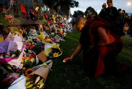 A man places a candle at a flower tribute area at Botanical Gardens in Christchurch, New Zealand, March 16, 2019. REUTERS/Edgar Su