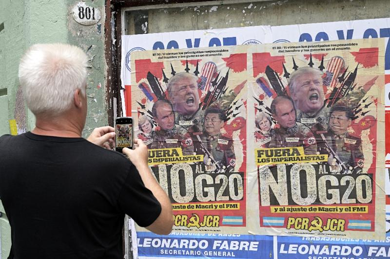 A passerby takes a picture of an anti-G20 Summit banner in downtown Buenos Aires (AFP Photo/Juan MABROMATA)