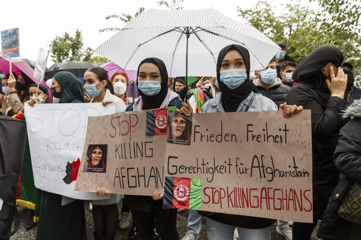 """Women hold signs reading """"Stop killing Afghans"""" and """"Peace, Freedom, Justice for Afghanistan"""" during a demonstration for the reception of threatened people from Afghanistan, in Hamburg, Germany, Sunday Aug. 22, 2021. (Markus Scholz/dpa via AP)"""