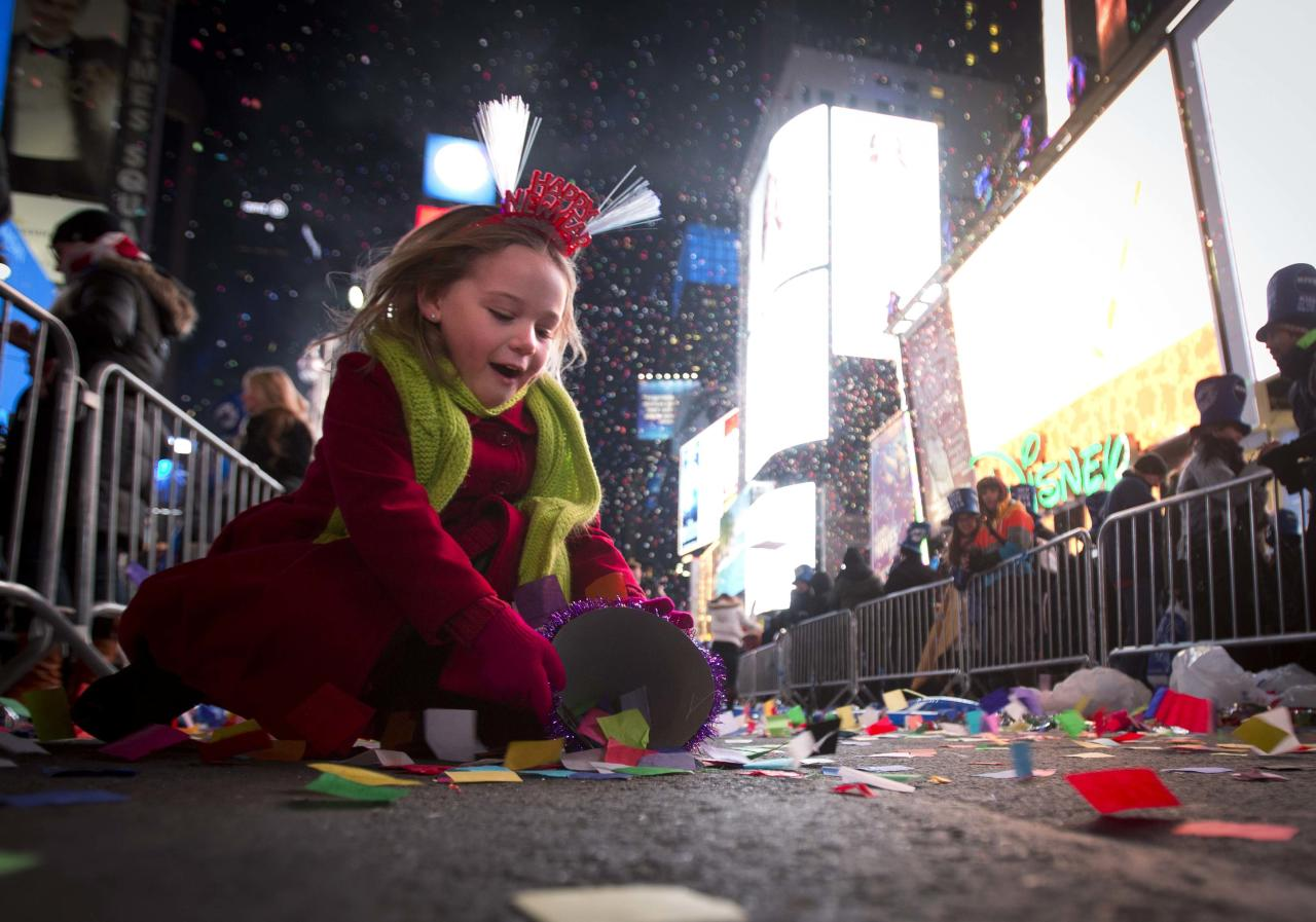 Maya Grace Hubbert, 5, collects confetti in a hat during New Year's Eve celebrations in Times Square in New York, January 1, 2014. REUTERS/Carlo Allegri (UNITED STATES - Tags: SOCIETY ANNIVERSARY)