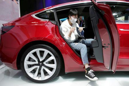 FILE PHOTO: A woman sits in a Tesla Model 3 car during a media preview at the Auto China 2018 motor show in Beijing, China April 25, 2018. REUTERS/Jason Lee/File Photo