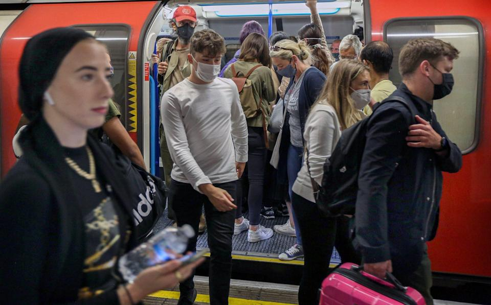 Passengers leave a busy underground train still wearing their facemasks in London - SOPA Images/LightRocket