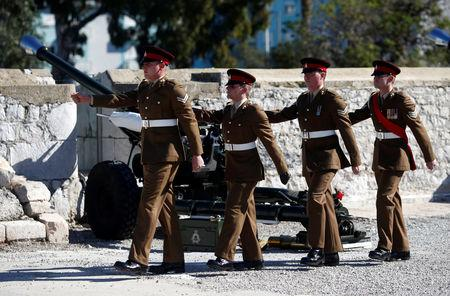 Members of the Royal Gibraltar Regiment march after firing a 21-gun salute to mark the 67th anniversary of Britain's Queen Elizabeth's accession to the throne, in front of the Rock in the British overseas territory of Gibraltar, historically claimed by Spain February 6, 2019. REUTERS/Jon Nazca