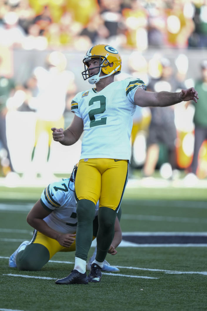 Green Bay Packers kicker Mason Crosby (2) kicks a winning field goal from the hold of Corey Bojorquez during overtime in an NFL football game against the Cincinnati Bengals in Cincinnati, Sunday, Oct. 10, 2021. (AP Photo/AJ Mast)