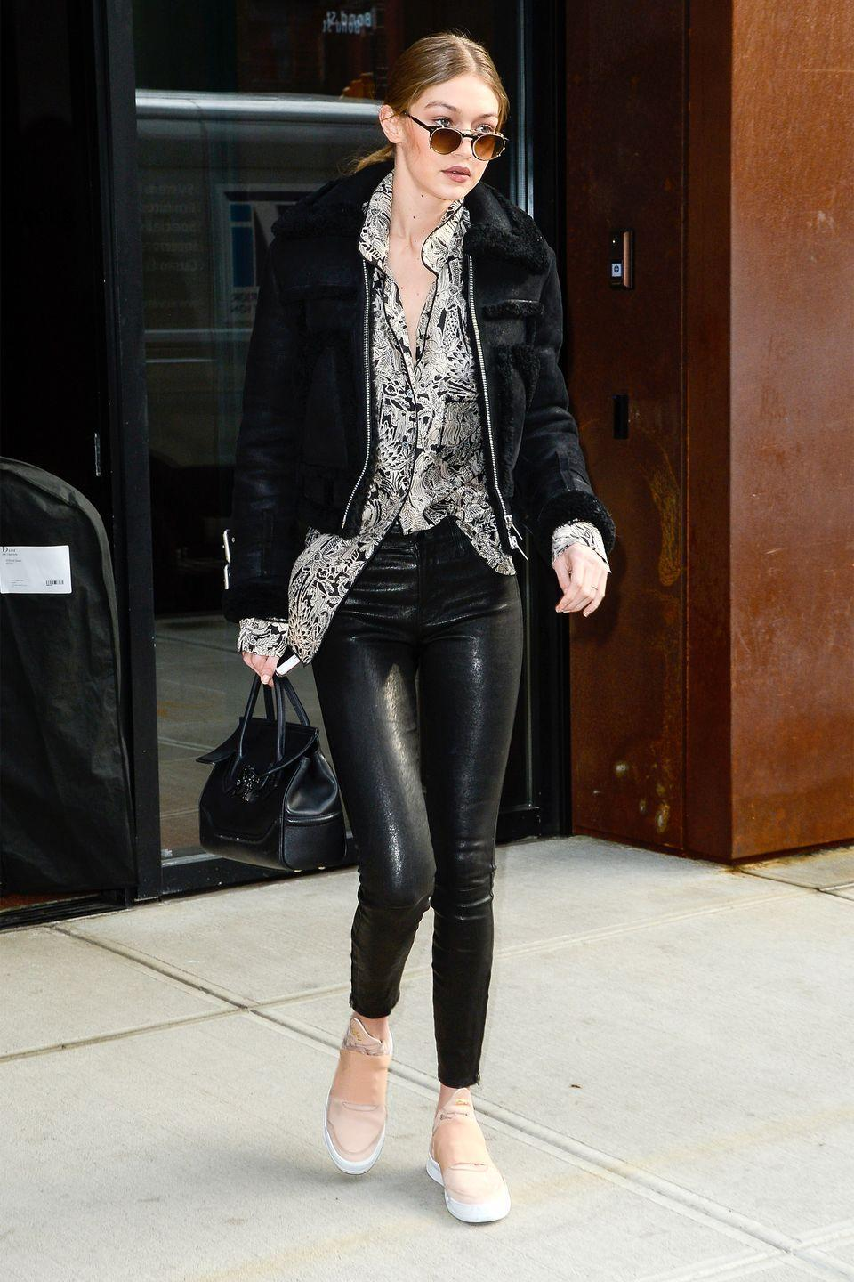 <p>In a black shearling jacket, printed blouse, leather pants, peach sneakers, Versace handbag and rounded sunglasses while out in New York. </p>
