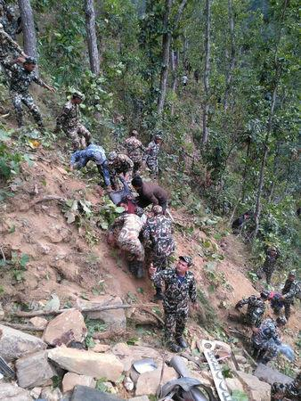 Nepalese army personnel assists a victim after an overcrowded bus veered off a hilly road in Jajarkot