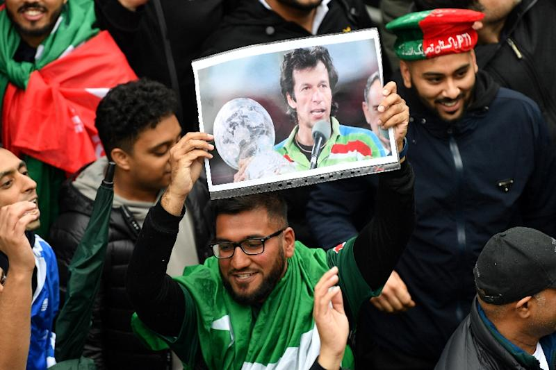 A Pakistan fan in England holds a picture of Prime Minister Imran Khan showing him as skipper of the team that won the 1992 World Cup