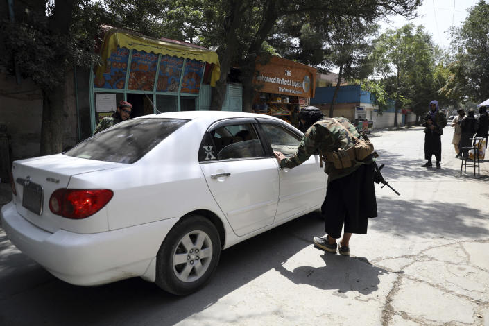Taliban fighters search a vehicle at a checkpoint on the road in the Wazir Akbar Khan neighborhood in the city of Kabul, Afghanistan, Sunday, Aug. 22, 2021. A panicked crush of people trying to enter Kabul's international airport killed several Afghan civilians in the crowds, the British military said Sunday, showing the danger still posed to those trying to flee the Taliban's takeover of the country. (AP Photo/Rahmat Gul)