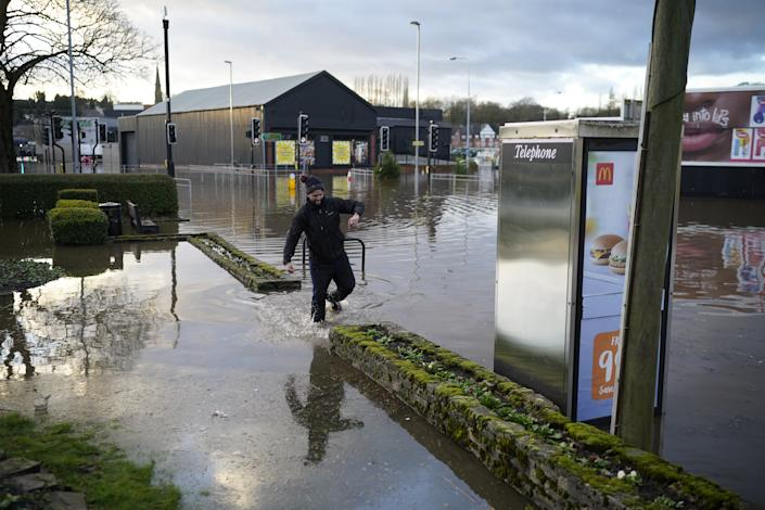 A man wades through the flood waters in NorthwichGetty