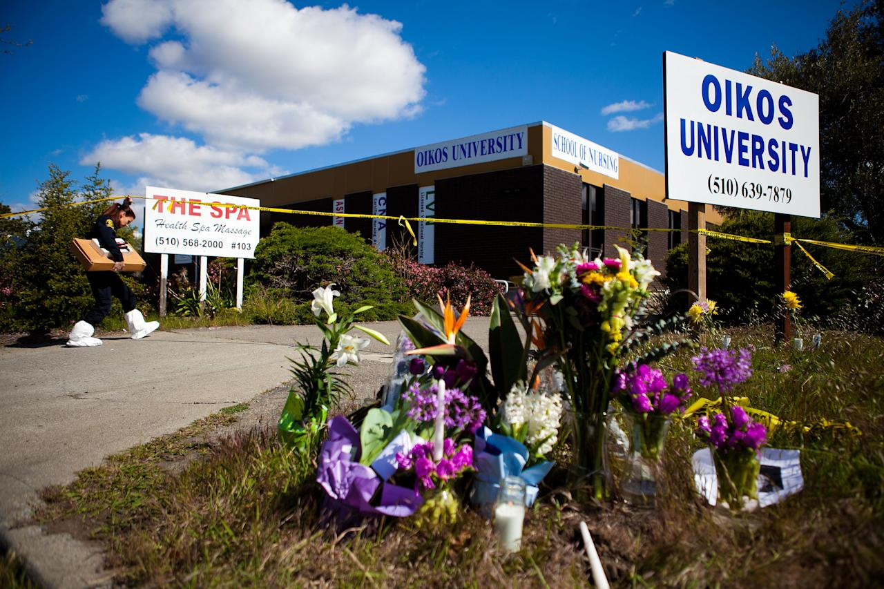 A member of the Oakland Police Crime Scene Investigation Unit walks past a makeshift memorial as she enters Oikos University where a gunman had gone on a shooting rampage, April 4, 2012 in Oakland, California. Six students and one employee were killed on Monday when a gunman opened fire at Christian-based Oikos University. The suspect One Goh, a former nursing student at the school, was arrested shortly after the shooting and is expected to make his first court appearance.  (Photo by Jonathan Gibby/Getty Images)