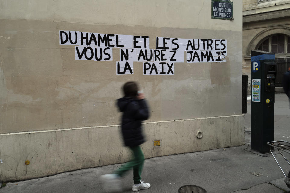 """Signs on the wall reads """"Duhamel, and the others, you will never be in peace"""" referring to prominent French political expert, Olivier Duhamel, in Paris, Tuesday, Jan. 19, 2021. The French government pledged on Thursday to toughen laws on the rape of children, as a massive online movement has seen hundreds of victims share accounts about sexual abuses within their families under the hashtag #MeTooInceste. (AP Photo/Francois Mori)"""