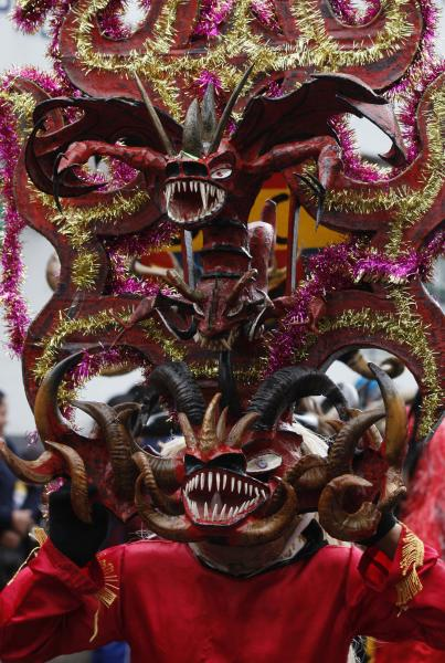 A man with a devil's mask dances in La Diablada in Pillaro, Ecuador, Monday, Jan. 6, 2014, to celebrate the end of the year and the start of the new one. The town of Pillaro kicks off the feast of La Diablada with neighborhoods competing to bring in as many people as possible dressed as different characters. Originally the devil costume was used to open up space to allow other participants to dance, but over the years the character gained popularity and became the soul of the feast. (AP Photo/Dolores Ochoa)
