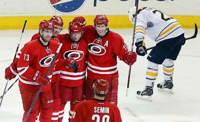 Carolina Hurricanes' Brett Bellemore (73), Ron Hainsey (65), Jordan Staal (11) and Alexander Semin (28), of Russia, congratulate teammate Jiri Tlusty (19) of the Czech Republic, on his go-ahead goal as Buffalo Sabres' Drew Stafford (21) skates past during the third period of an NHL hockey game in Raleigh, N.C., Thursday, March 13, 2014. The Hurricanes won 4-2. (AP Photo/Karl B DeBlaker)